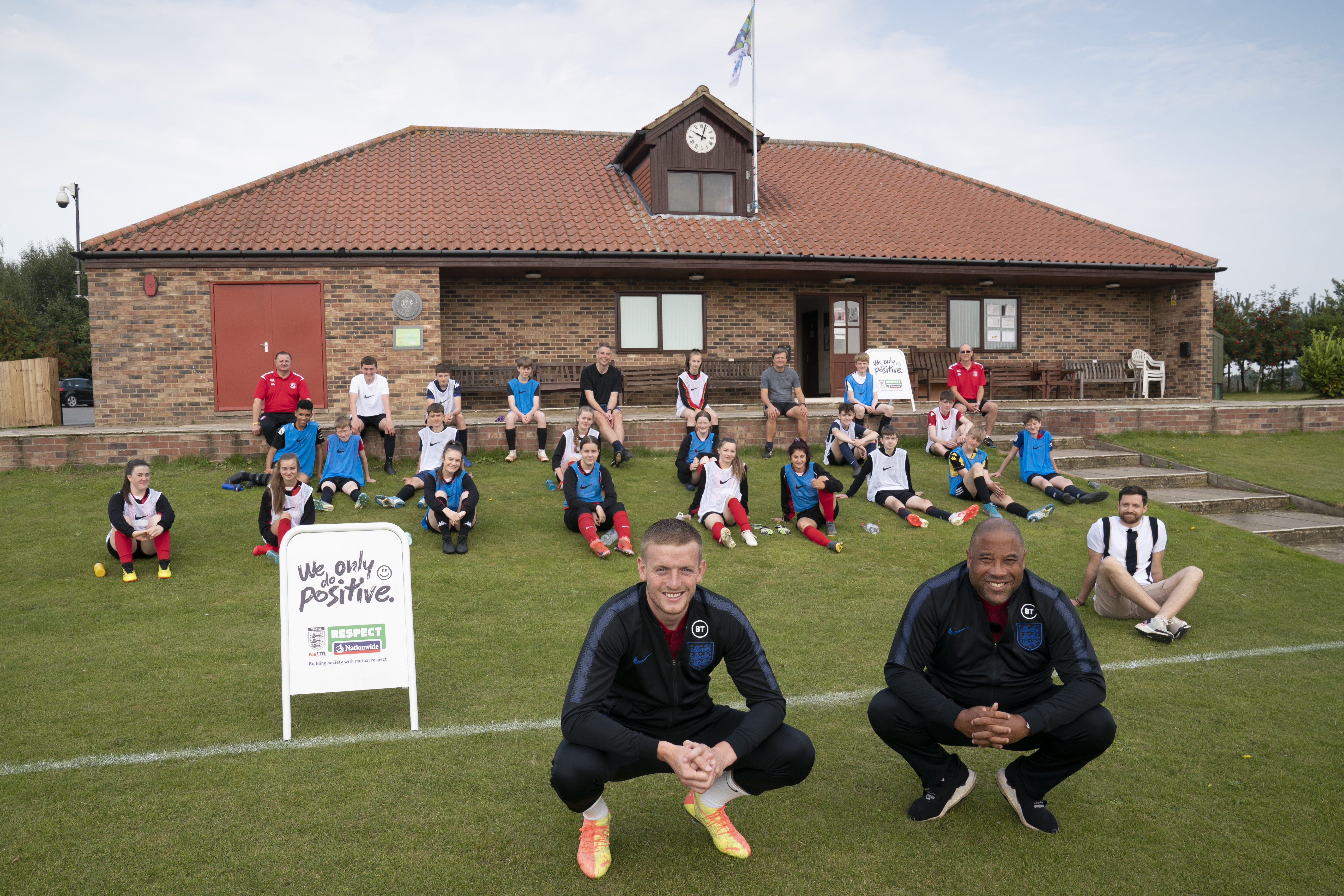 John Barnes and Jordan Pickford with children playing football