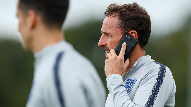 Expand The Three Lions boss takes a call during training on Sunday morning