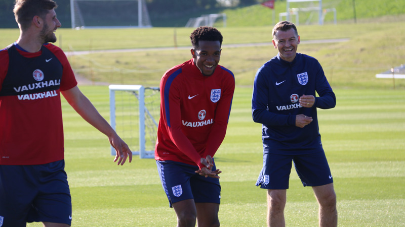 England Under-21s coach Colin Cooper shares a joke with Kasey Palmer and Jack Stephens in training