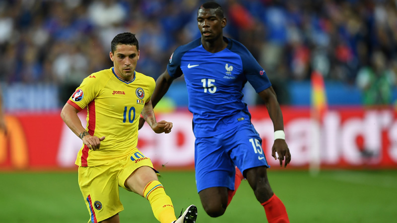 Nicolae Stanciu of Romania and Paul Pogba of France compete for the ball