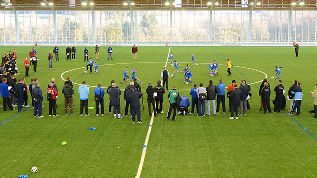 Coaches from around the country observe a training session on the indoor 3G pitch at St. George's Park