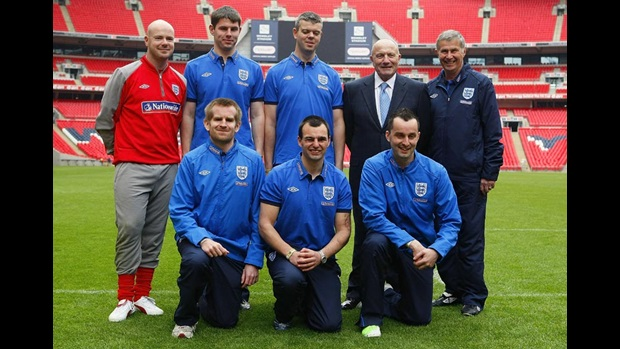 The England Blind squad line-up alongside George Cohen on the Wembley pitch.