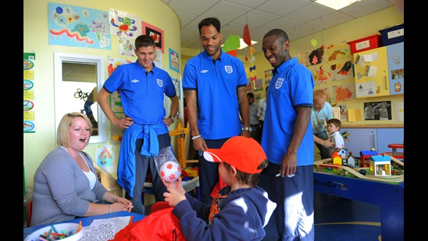The England players look on as a young patient opens a gift.