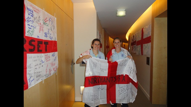 Karen Carney (left) and Kelly Smith wrap themselves in a 'good luck' flag sent to Germany by the Northants FA.