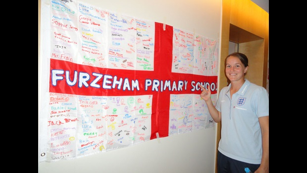 The flag sent to the World Cup by Furzeham Primary School gets Casey Stoney's approval.