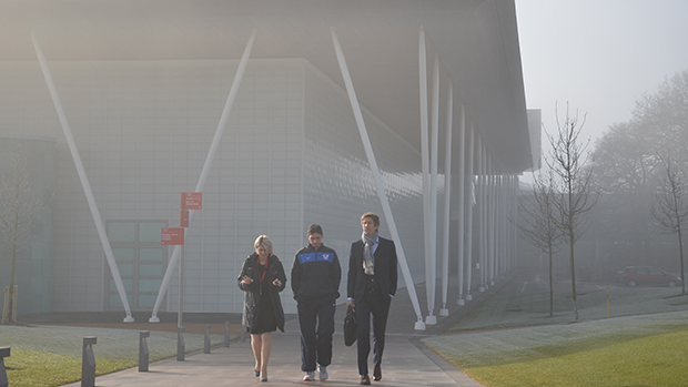 Edwin van der Sar walks from a cloud covered football centre to the hotels